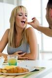 Pares jovenes felices que gozan del desayuno en la cocina Imágenes de archivo libres de regalías