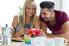 Pares jovenes felices que gozan del desayuno en la cocina Fotografía de archivo libre de regalías
