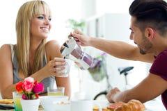 Pares jovenes felices que gozan del desayuno en la cocina Fotos de archivo