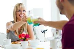 Pares jovenes felices que gozan del desayuno en la cocina Imagen de archivo libre de regalías