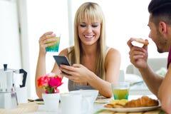 Pares jovenes felices que gozan del desayuno en la cocina Imagenes de archivo