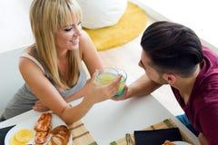 Pares jovenes felices que gozan del desayuno en la cocina Foto de archivo libre de regalías