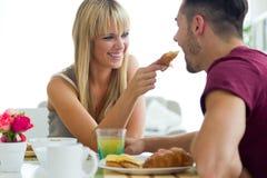 Pares jovenes felices que gozan del desayuno en la cocina Fotos de archivo libres de regalías