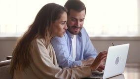 Pares jovenes felices que hablan haciendo compras de Internet usando el ordenador portátil almacen de video