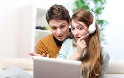 Pares jovenes felices que hablan a través del ordenador con la charla video Fotografía de archivo