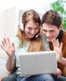 Pares jovenes felices que hablan a través del ordenador con la charla video Imagen de archivo libre de regalías