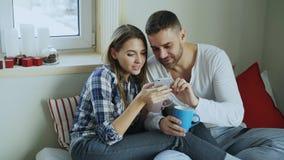 Pares jovenes felices que hablan y que hojean medios sociales en smartphone mientras que se sienta adentro en coffe de la cama y  fotos de archivo libres de regalías