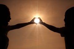 Pares jovenes felices que hacen dimensión de una variable del corazón Imagen de archivo libre de regalías