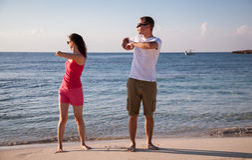 Pares jovenes felices que hacen ejercicios en la costa de mar Imágenes de archivo libres de regalías