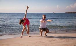 Pares jovenes felices que hacen ejercicios en la costa de mar Fotografía de archivo libre de regalías