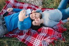 Pares jovenes felices que hacen el selfie cerca del mar fotos de archivo