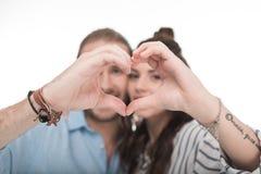 Pares jovenes felices que hacen gesto del corazón de la mano Fotografía de archivo