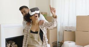 Pares jovenes felices que hacen viaje virtual en el nuevo apartamento fotos de archivo