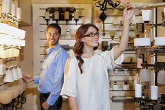 Pares jovenes felices que hojean para los accesorios en tienda de las luces Foto de archivo