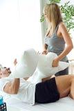 Pares jovenes felices que juegan con las almohadas en el sofá Imagen de archivo libre de regalías