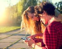 Pares jovenes felices que juegan en la tableta junto Fotografía de archivo