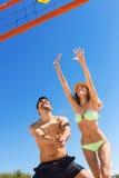 Pares jovenes felices que juegan a voleibol Foto de archivo