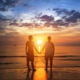 Pares jovenes felices que llevan a cabo las manos en la playa del mar durante la puesta del sol hermosa Imagenes de archivo
