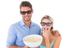 Pares jovenes felices que llevan los vidrios 3d que comen las palomitas Imagenes de archivo