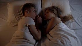 Pares jovenes felices que mienten en cama en la noche y que llevan a cabo las manos, relaciones fuertes foto de archivo