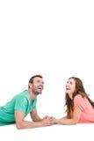 Pares jovenes felices que mienten en el piso que mira para arriba Foto de archivo libre de regalías