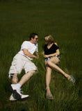 Pares jovenes felices que mienten en hierba en día asoleado fotos de archivo