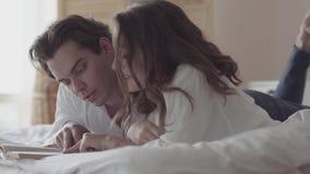 Pares jovenes felices que mienten en la cama que lee el primer del libro Mujer hermosa y hombre que pasan tiempo en cama en casa almacen de metraje de vídeo