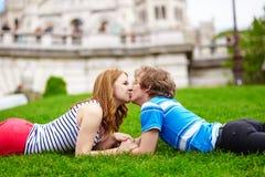 Pares jovenes felices que mienten en la hierba y besarse Imagen de archivo libre de regalías
