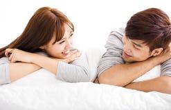 Pares jovenes felices que mienten en una cama Imagen de archivo libre de regalías