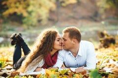 Pares jovenes felices que mienten entre las hojas de otoño en el parque Imagen de archivo