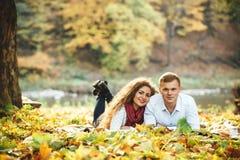 Pares jovenes felices que mienten entre las hojas de otoño en el parque Imagenes de archivo
