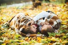 Pares jovenes felices que mienten entre las hojas de otoño en el parque Fotos de archivo libres de regalías
