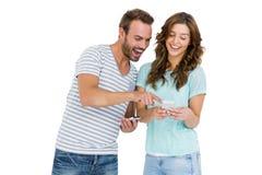 Pares jovenes felices que miran el teléfono móvil Imagen de archivo