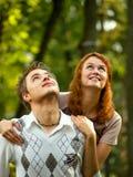 Pares jovenes felices que miran hacia arriba Foto de archivo