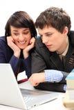 Pares jovenes felices que miran la computadora portátil. Foto de archivo