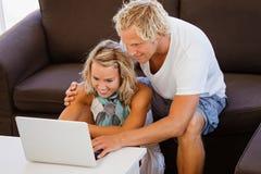 Pares jovenes felices que miran la computadora portátil Imagen de archivo libre de regalías
