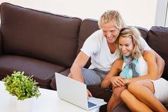 Pares jovenes felices que miran la computadora portátil Foto de archivo