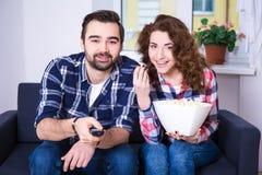 Pares jovenes felices que miran la TV o la película en casa Foto de archivo libre de regalías