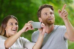 Pares jovenes felices que miran para arriba en el asombro y que toman la fotografía foto de archivo libre de regalías