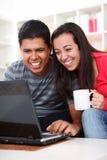 Pares jovenes felices que miran una computadora portátil Imagenes de archivo