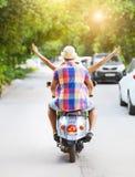 Pares jovenes felices que montan una vespa del vintage en el wearin de la calle Foto de archivo libre de regalías