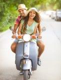 Pares jovenes felices que montan una vespa del vintage en el wearin de la calle Imágenes de archivo libres de regalías