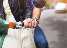 Pares jovenes felices que montan una vespa del vintage en la calle Foto de archivo libre de regalías