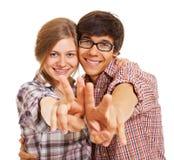 Pares jovenes felices que muestran la muestra de v Foto de archivo