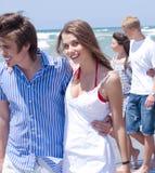 Pares jovenes felices que recorren en la playa Imágenes de archivo libres de regalías