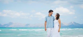 Pares jovenes felices que recorren en la playa Foto de archivo libre de regalías