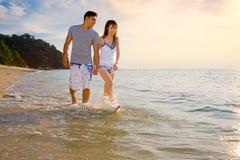 Pares jovenes felices que recorren a lo largo de la playa Imágenes de archivo libres de regalías