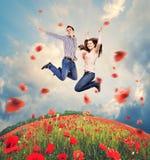 Pares jovenes felices que saltan en campo de las amapolas Imagen de archivo