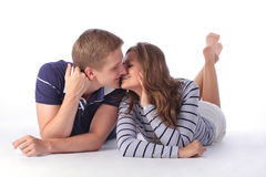 Pares jovenes felices que se acuestan en el piso y besarse Imagen de archivo libre de regalías