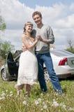 Pares jovenes felices que se colocan cerca del coche Fotos de archivo